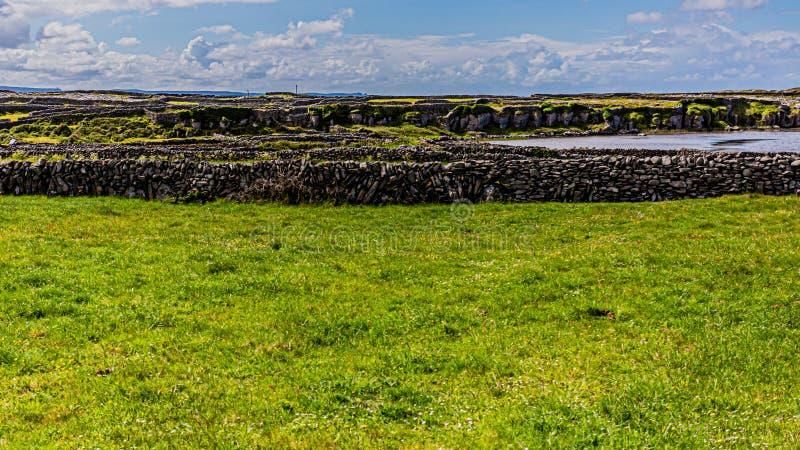 Paisagem irlandesa com cercas de calcário na ilha de Inis Oirr com uma pequena praia ao fundo imagens de stock royalty free