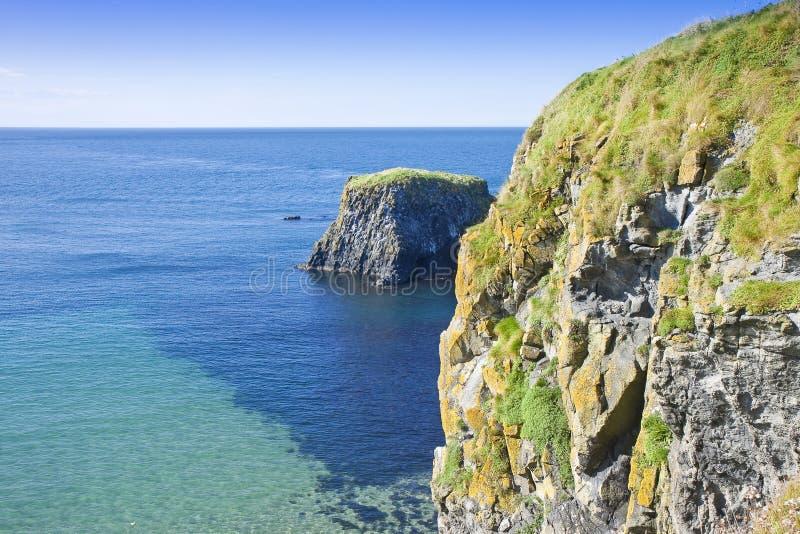 Paisagem irlandesa em Irlanda do Norte com blocos de rochas do basalto no condado Antrim - Reino Unido do mar imagem de stock