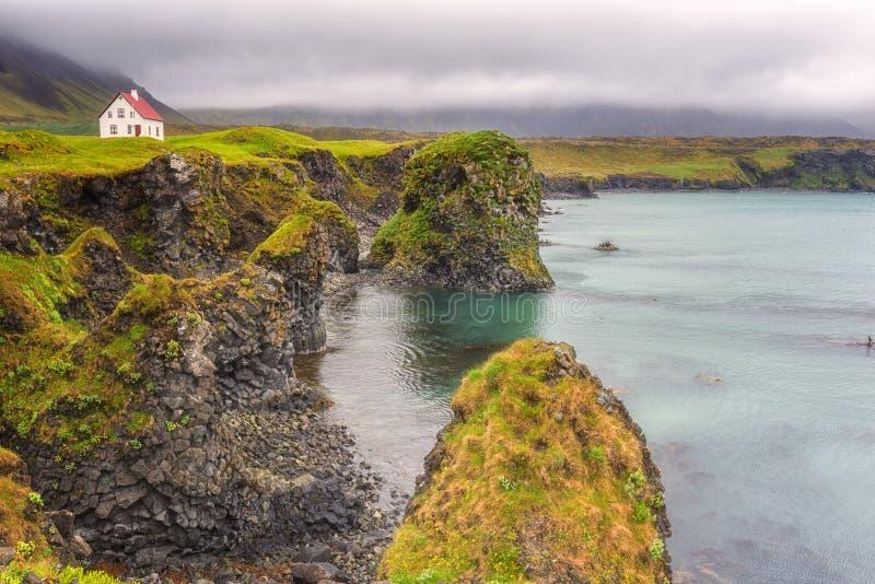 Paisagem islandêsa, casa só no seacoast vulcânico dos penhascos, Arnarstapi, península de Snaefellsnes, Islândia imagens de stock