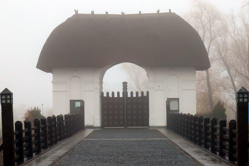 Paisagem Mystical Ponte de pedra romântica bonita com trilhos e porta de madeira Entrada ao castelo velho com telhado cobrido com imagem de stock