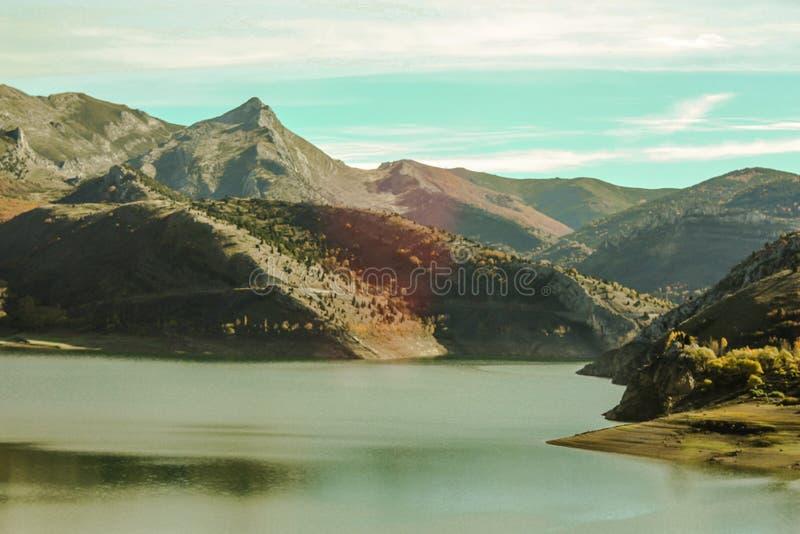 Paisagem natural montanhosa com o lago no primeiro plano, terra de cores diferentes imagem de stock royalty free