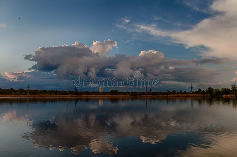 Paisagem nebulosa bonita com as nuvens refletidas na água na primavera em Ucrânia fotografia de stock