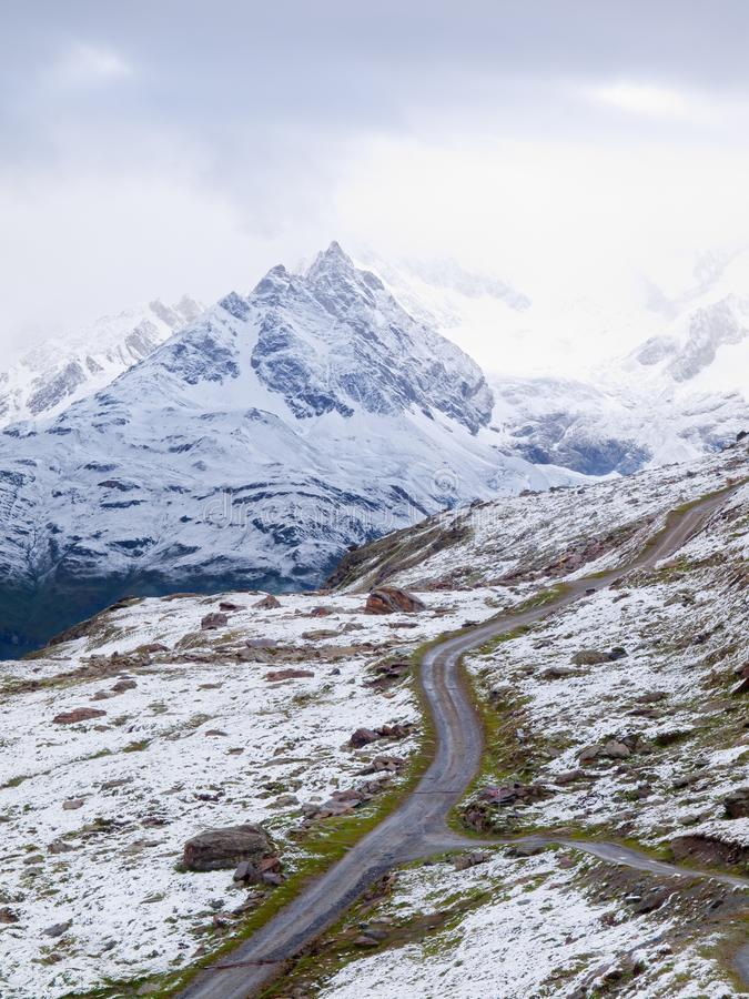Paisagem nevado com estrada gravelosa Picos afiados enevoados das montanhas altas no fundo fotografia de stock royalty free