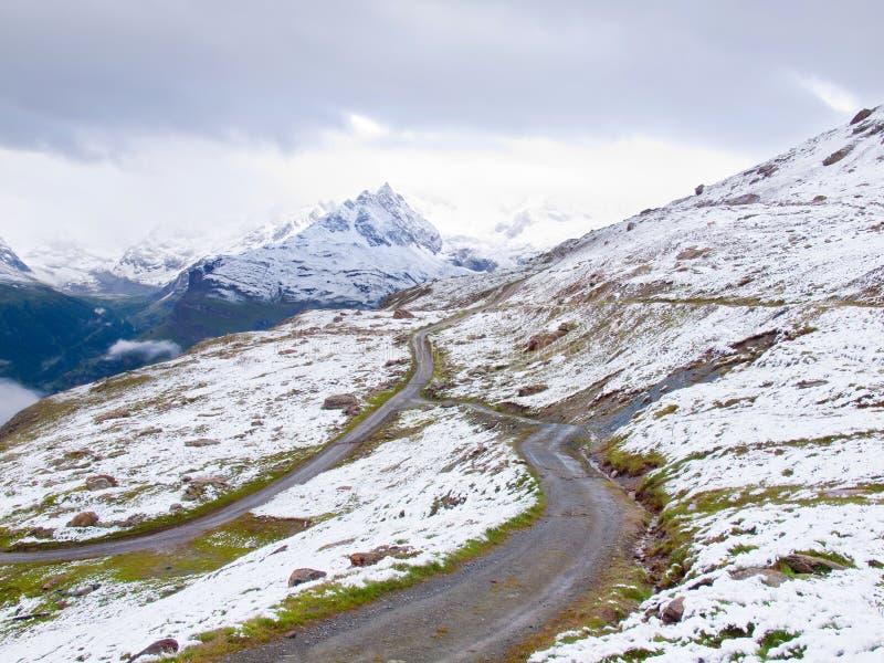 Paisagem nevado com estrada gravelosa Picos afiados enevoados das montanhas altas no fundo fotos de stock royalty free