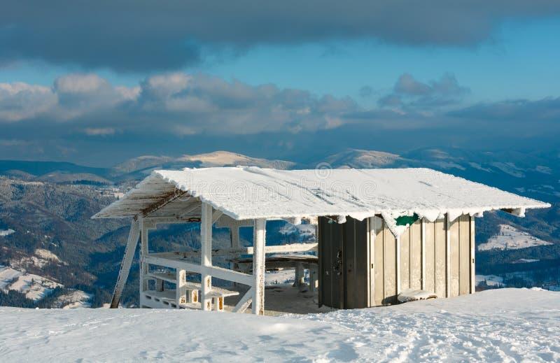 Paisagem nevado da montanha do inverno com plataforma de madeira pequena e c fotografia de stock royalty free