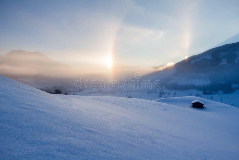 Paisagem nevado nos cumes, nascer do sol do inverno com fenômenos do halo fotos de stock