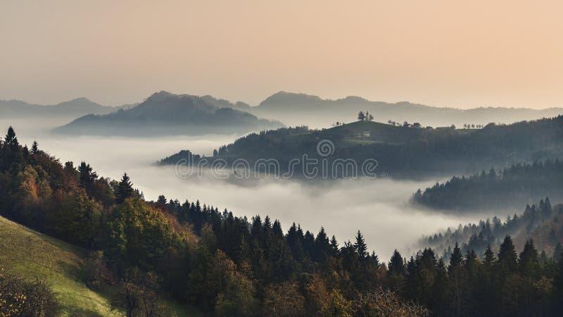 Paisagem nevoenta da montanha no alvorecer Cenário do outono slovenia imagem de stock
