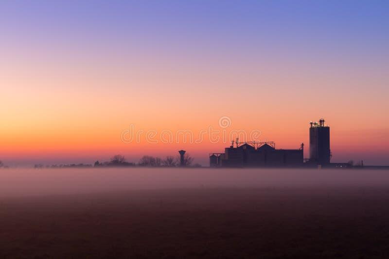 Paisagem nevoenta industrial, silhueta da fábrica velha contra o céu do por do sol e a névoa na hora azul na noite foto de stock