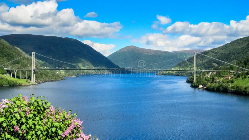 Paisagem norueguesa com vista geral de uma ponte de suspensão que cruza um fiorde e uma luz solar branca dispersada das nuvens na fotos de stock