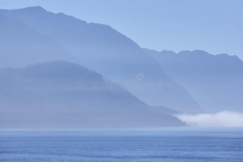 Paisagem norueguesa do fiorde no alvorecer no tom azul Destaque de Noruega fotos de stock royalty free