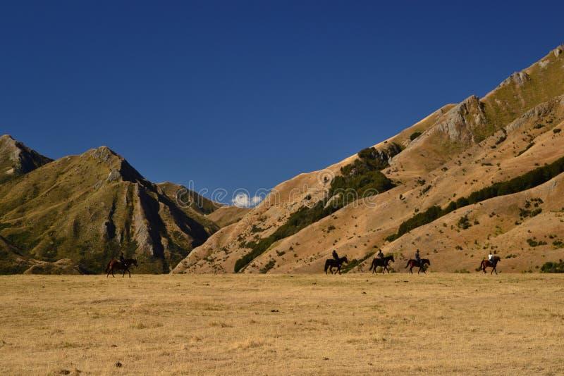 Paisagem ocidental selvagem, cavaleiros em cavalos, montanhas secas, savanas, terra do deserto imagem de stock