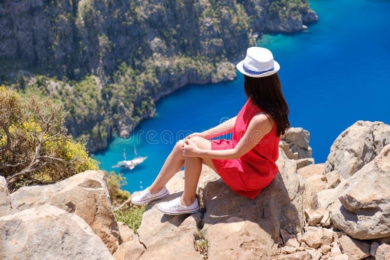 A paisagem Oludeniz, Turquia, uma mo?a em um vestido vermelho olha o Butterfly Valley de cima de, sentando-se nas rochas foto de stock