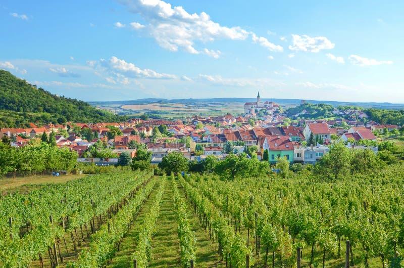 Paisagem panorâmico bonita com fileiras dos vinhedos em torno da cidade checa pitoresca Mikulov com o castelo dominante de Mikulo fotos de stock royalty free