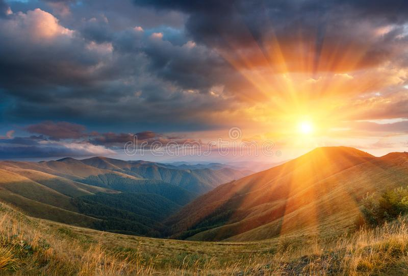 Paisagem panorâmico do por do sol fantástico nas montanhas A vista dos montes do outono iluminou-se pelos raios do sol da noite fotografia de stock