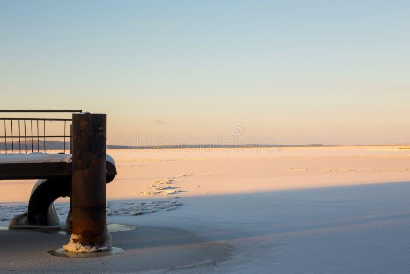 Paisagem pictórico do inverno do rio congelado iluminado pelo sol vermelho e pelo céu nebuloso infinito com a peça do cais cobert imagens de stock