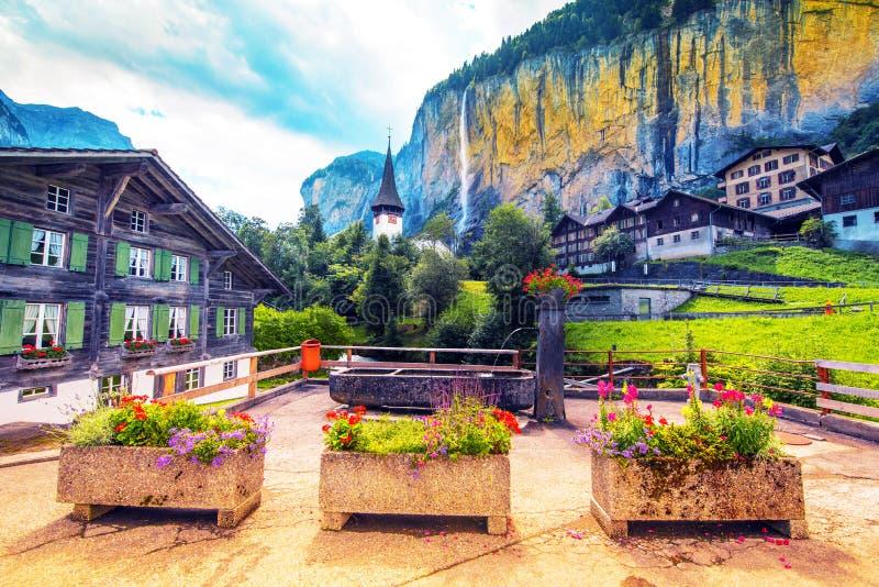 A paisagem pitoresca com flores, uma cachoeira e a igreja da garganta em Lauterbrunnen nos cumes su??os, Su??a, Europa foto de stock