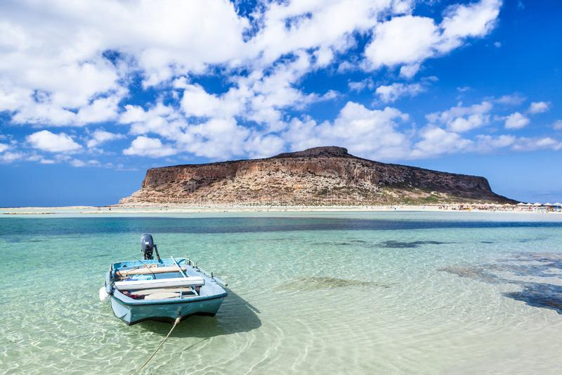 Paisagem romântica com o barco de enfileiramento de madeira pequeno na baía de Balos, Grécia foto de stock royalty free