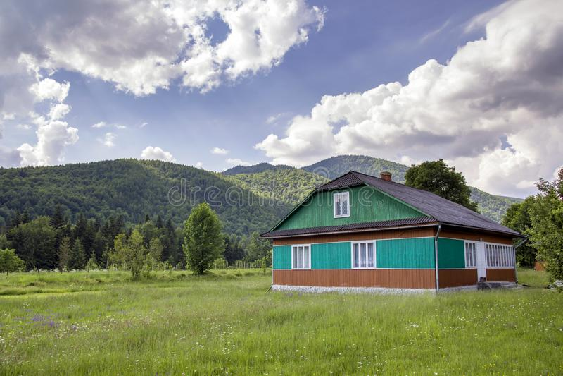 Paisagem rural calma do verão no dia ensolarado brilhante Lit pela casa residencial de madeira bonita do sol pintada no verde, no fotos de stock royalty free
