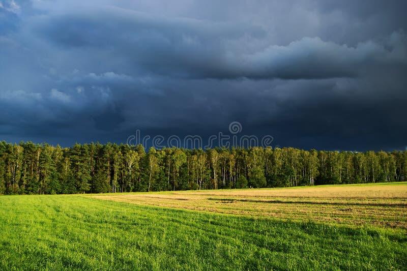 Paisagem rural com o céu dramático escuro após a tempestade do verão imagem de stock