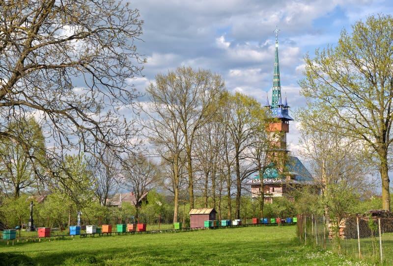 Paisagem rural da mola com a igreja neogótica dos maramures tradicionais na vila de Sapanta, Romênia imagens de stock royalty free