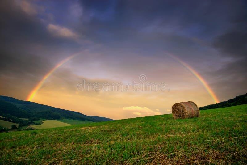 Paisagem rural do arco-íris com campo e pacote do feno Monte típico perto da vila em horas de verão, Eslováquia do slovak imagens de stock
