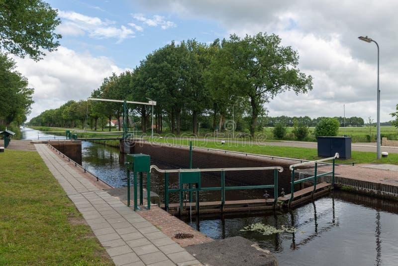 Paisagem rural holandesa com canal e a comporta velha imagem de stock