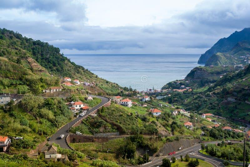 Paisagem típica da ilha de Madeira, da estrada serpentina da montanha, das casas nos montes e da vista para o mar imagem de stock