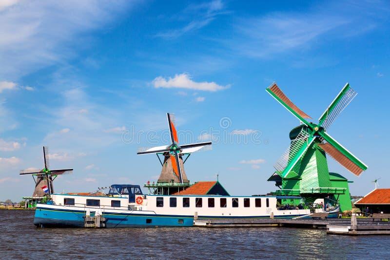 Paisagem típica do Dutch Moinhos de vento holandeses velhos tradicionais com navio de cruzeiros e o céu azul na vila de Zaanse Sc fotografia de stock