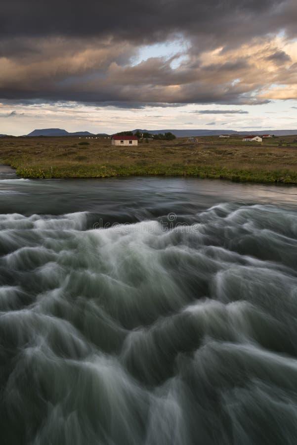 Paisagem típica em Islândia com uma casa só no por do sol imagens de stock royalty free