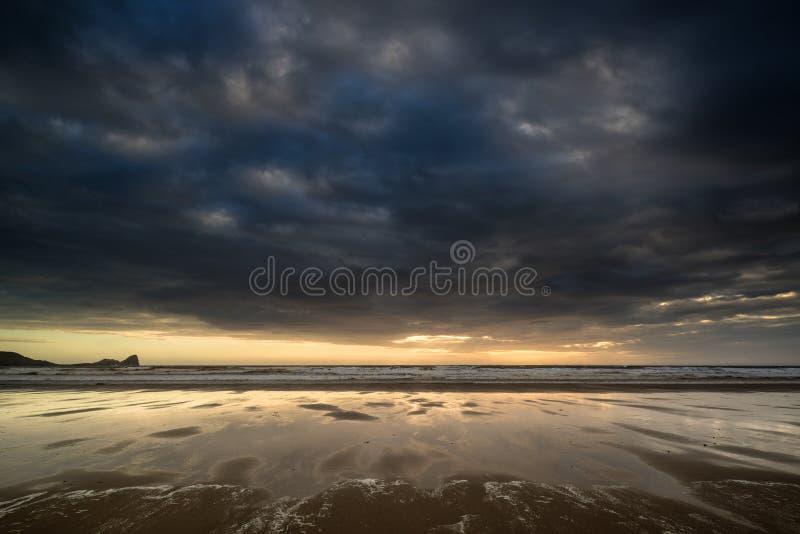 A paisagem tormentoso dramática do céu refletiu na água da maré baixa no ró fotos de stock