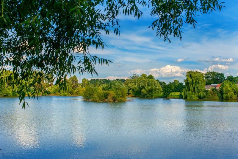 A paisagem tranquilo em um lago, com o céu vibrante e limpa a água azul imagens de stock royalty free