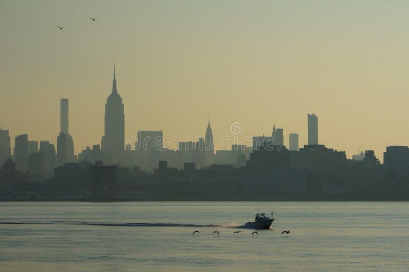 Paisagem urbana dos arranha-céus de Manhattan, New York, com corredor do cortador e voo dos pássaros baixo acima da água adiante fotografia de stock
