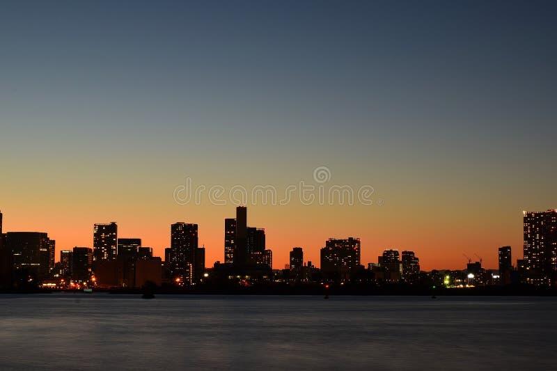 Paisagem urbana em torno da água da baía no crepúsculo imagens de stock