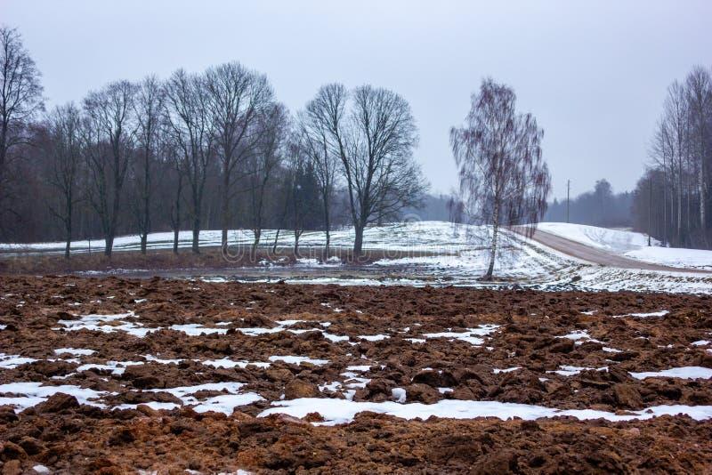 Paisagem vazia do campo no dia de inverno nebuloso com a neve que cobre em parte a terra e a névoa fotos de stock