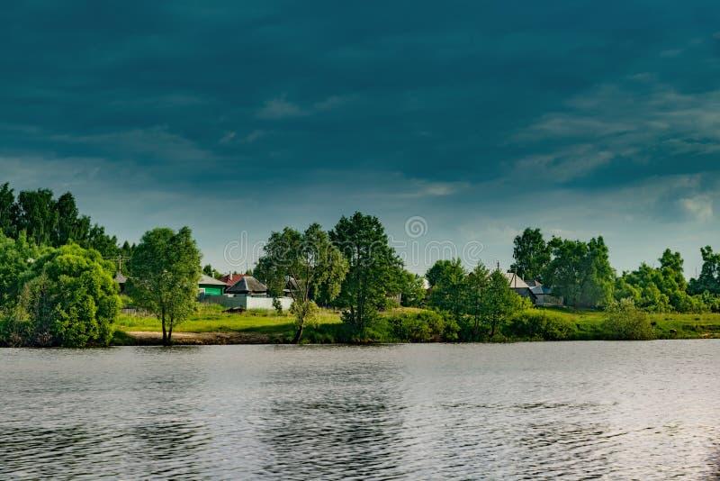 Paisagem, verão bonito Uma vila no banco de um rio largo, bonito, nuvens de cúmulo em um céu azul em um dia de verão imagem de stock royalty free