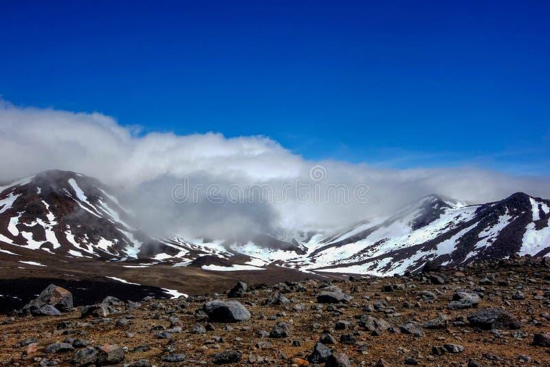 Paisagem vulcânica com as montanhas cobertas por nuvens de suspensão do ponto baixo de Snowand fotos de stock