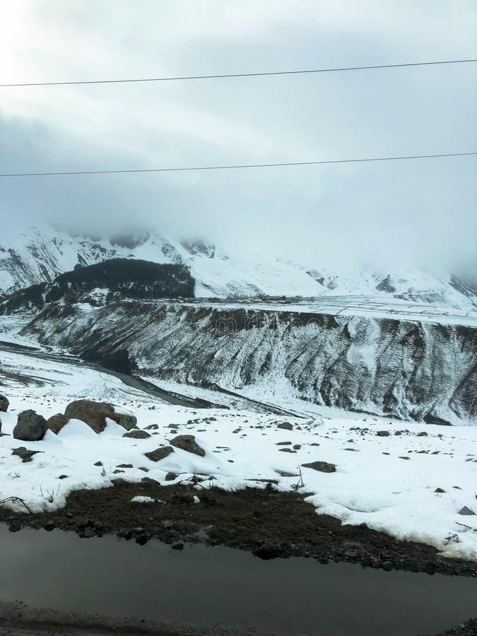 Paisagens frias do recurso do inverno da montanha bonita com n?voa dos picos de montanha alta e as rochas cobertos de neve para a fotografia de stock royalty free