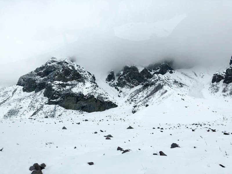 Paisagens frias do recurso do inverno da montanha bonita com n?voa dos picos de montanha alta e as rochas cobertos de neve para a imagem de stock royalty free