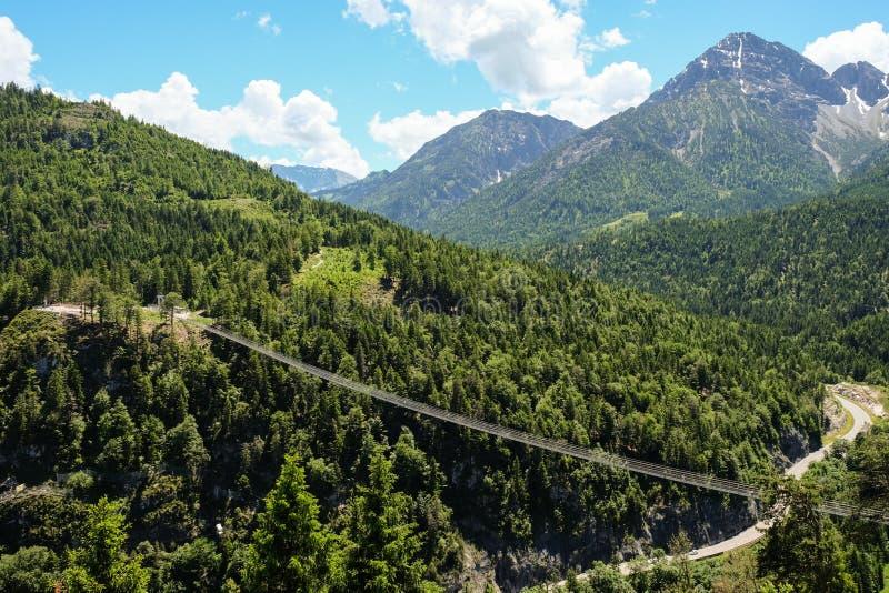 Paisaje épico de la montaña con puente colgante y las montañas en el fondo imágenes de archivo libres de regalías