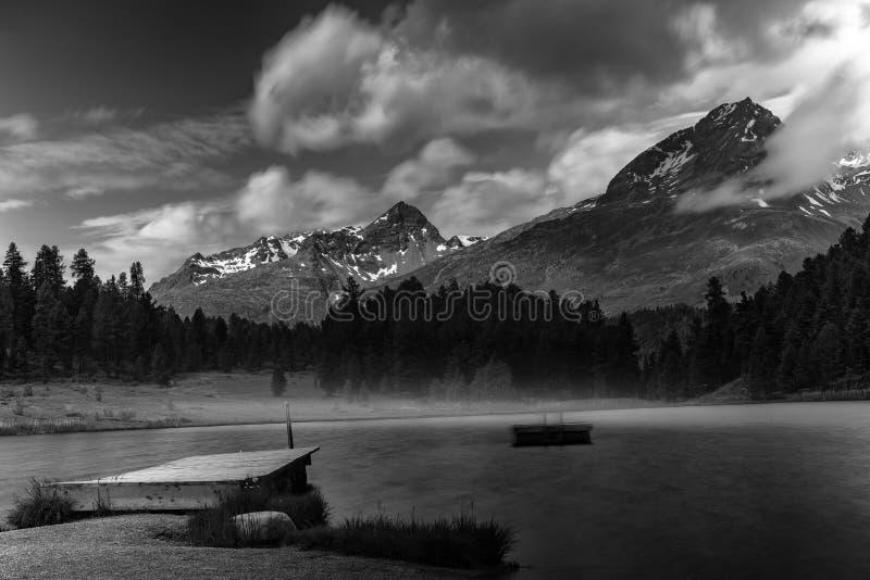Paisaje alpino con el lago de la montaña en bella arte blanco y negro fotos de archivo