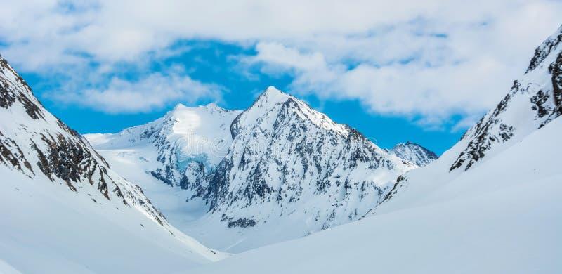 Paisaje alpino con los picos cubiertos por la nieve y las nubes imágenes de archivo libres de regalías