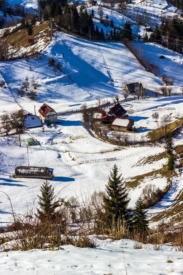 Paisaje alpino del invierno soleado con el pequeño pueblo rumano en el valle de Bucegi imagenes de archivo