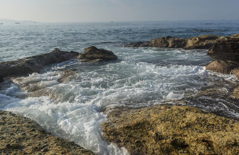 Paisaje asombroso hermoso de la orilla rocosa con las ondas en la playa en la ciudad de Weligama fotografía de archivo