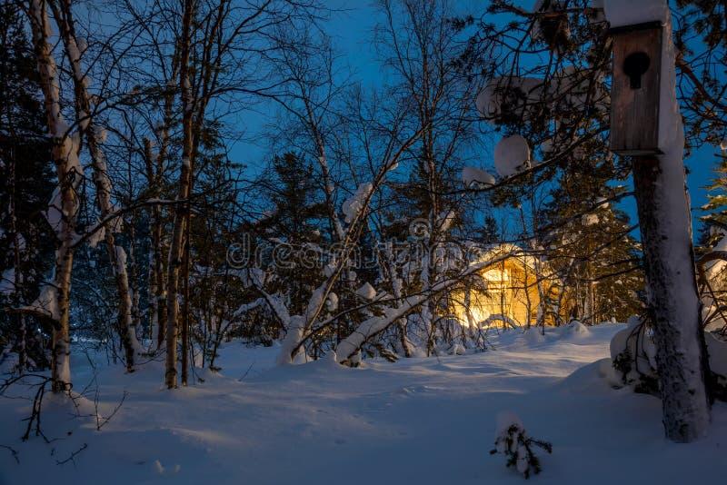 Paisaje azul de la noche del invierno, casa de madera caliente imágenes de archivo libres de regalías