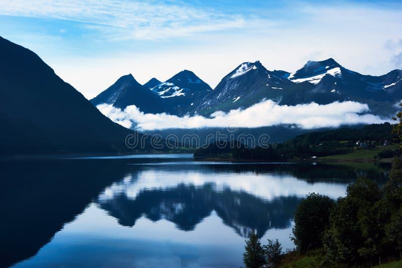 Paisaje azul hermoso con las montañas coronadas de nieve y su reflexión en agua imagen de archivo libre de regalías