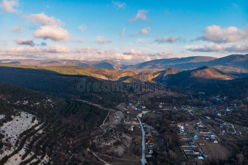 Paisaje bajo aéreo con el pequeño pueblo rural en valle en la puesta del sol, paisaje hermoso de la montaña de la naturaleza desd fotografía de archivo