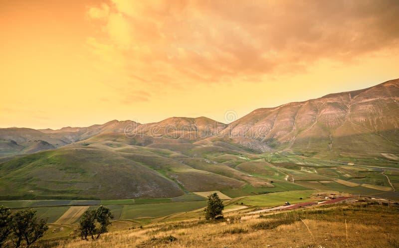 Paisaje caliente de la puesta del sol Montañas y fondo de los campos Italia foto de archivo