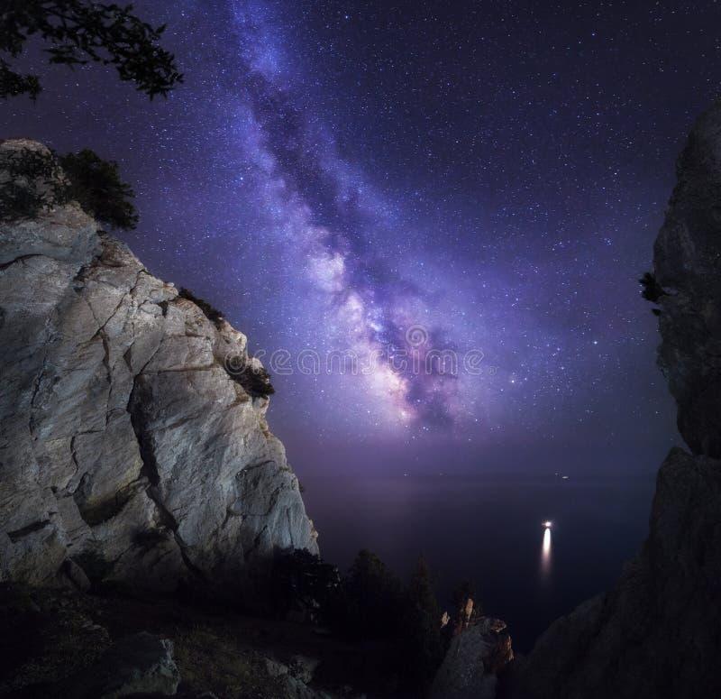 Paisaje colorido hermoso de la noche con la vía láctea, las rocas, el mar y el cielo estrellado Paisaje de la montaña Universo as imagen de archivo