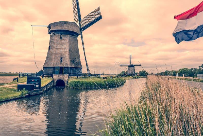 Paisaje con dos molinoes de viento y la bandera holandesa Oterleek Países Bajos Holanda imagenes de archivo