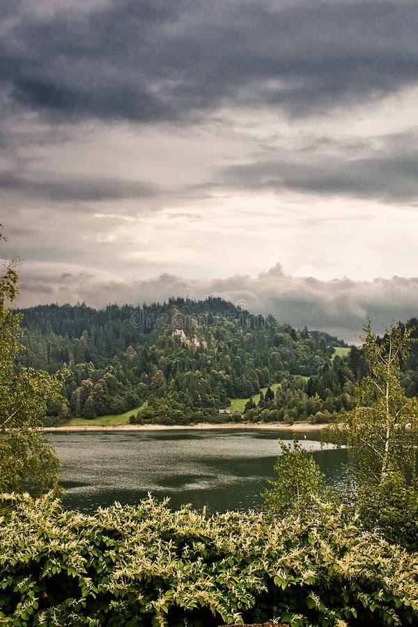Paisaje con el cielo nublado, el lago y las montañas foto de archivo libre de regalías